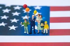 Gente miniatura, familia americana feliz que sostiene el globo con Uni Fotos de archivo