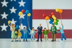 Gente miniatura, familia americana feliz que sostiene el globo con Uni Fotos de archivo libres de regalías