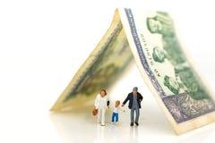 Gente miniatura: Familia que camina con el dinero usando como concepto de la seguridad de la familia Imagen de archivo libre de regalías