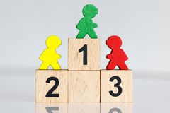 Gente miniatura: figuras coloridas que se colocan en el podio de madera 1,2,3 con el equipo del negocio Imágenes de archivo libres de regalías
