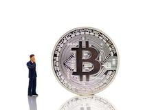 Gente miniatura: hombre de negocios que busca el dinero del hallazgo con el bitcoin Foto de archivo libre de regalías