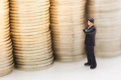 Gente miniatura, hombre de negocios que busca la pila de monedas usando como crecimiento de dinero del fondo para arriba, ahorro, Imagen de archivo libre de regalías