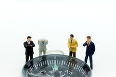Gente miniatura: Hombre de negocios que se coloca con el compás Uso de la imagen para la dirección de la economía, inversión para Fotos de archivo libres de regalías
