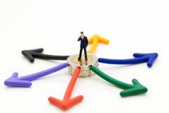 Gente miniatura: Hombre de negocios que se coloca delante de la opción del camino de la flecha Uso de la imagen para el concepto  Imágenes de archivo libres de regalías