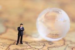 Gente miniatura: hombre de negocios que se coloca en un mapa del mundo, pensando en cómo hacer la ventaja del aumento para el neg Fotos de archivo