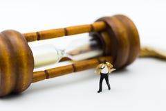 Gente miniatura: hombre de negocios y lazo que soplan en viento con reloj de arena Uso de la imagen para el concepto del negocio Fotografía de archivo libre de regalías