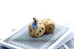 Gente miniatura: Hombre que se sienta en Rolls que un de madera corta en cuadritos con la moneda Fotos de archivo libres de regalías
