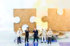 Gente miniatura, hombres de negocios del grupo que se colocan en el juego de ajedrez con el fondo del rompecabezas, solución de p Fotos de archivo libres de regalías