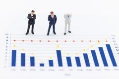 Gente miniatura: Hombres de negocios que miran la ventaja del trabajo del progreso del gráfico Uso como concepto del negocio Fotografía de archivo libre de regalías