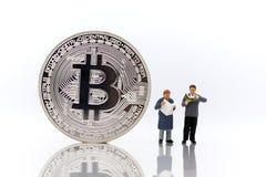 Gente miniatura: Hombres que leen para el dinero del hallazgo con el bitcoin en el fondo blanco fotos de archivo