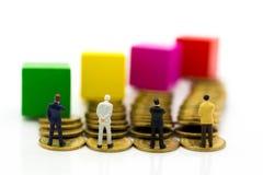 Gente miniatura: Il grafico che mostra la prestazione, profitti ha generato la b immagine stock