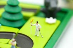 Gente miniatura: il supporto del giocatore di golf con il ` s dei bambini gioca la raccolta, Fotografia Stock