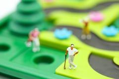 Gente miniatura: il supporto del giocatore di golf con il ` s dei bambini gioca la raccolta, Fotografia Stock Libera da Diritti