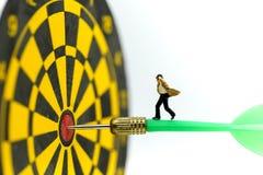 Gente miniatura: l'uomo d'affari sulla freccia del dardo che colpisce nel centro del bersaglio, affare dell'obiettivo, raggiunge  immagine stock