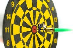 Gente miniatura: l'uomo d'affari sulla freccia del dardo che colpisce nel centro del bersaglio, affare dell'obiettivo, raggiunge  immagine stock libera da diritti