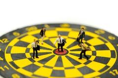Gente miniatura: l'uomo d'affari sulla freccia del dardo che colpisce nel centro del bersaglio, affare dell'obiettivo, raggiunge  immagini stock libere da diritti