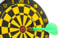 Gente miniatura: l'uomo d'affari sulla freccia del dardo che colpisce nel centro del bersaglio, affare dell'obiettivo, raggiunge  fotografia stock