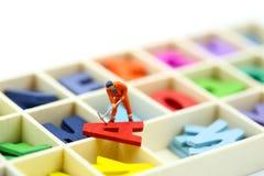 Gente miniatura: Lavoratore con alphabe inglese di legno variopinto, e Fotografie Stock