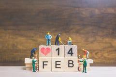 Gente miniatura: Lavoratore team-building parola ` ` del 14 febbraio sul blocco di legno Immagini Stock