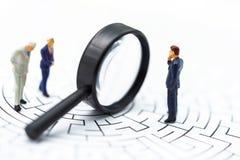 Gente miniatura: Lente d'ingrandimento di uso dell'uomo d'affari per trovare l'itinerario sul labirinto Concetti di individuazion immagini stock