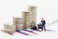 Gente miniatura: Los hombres de negocios ganan los beneficios del trabajo, monedas de la pila se colocan en el gráfico Uso como c Imagen de archivo
