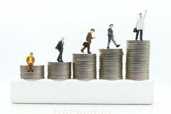 Gente miniatura: Los hombres de negocios que se colocan en una moneda apilada aumentan para arriba respectivamente, utilizado com Imagen de archivo libre de regalías