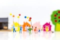 Gente miniatura: los niños llevan a cabo los globos, y el juego junto, usi Fotografía de archivo