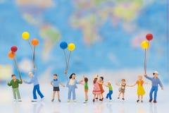 Gente miniatura: los niños sostienen los globos, y el juego junto, fondo es mapa del mundo Foto de archivo