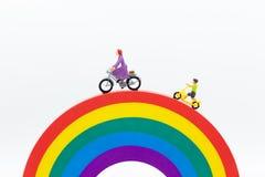 Gente miniatura: Mamma e bambini che ciclano sull'arcobaleno Uso di immagine per essere buon modello, concetto 'nucleo familiare' immagini stock libere da diritti
