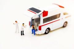 Gente miniatura: Medico e condizione paziente con l'ambulanza Lui fotografia stock libera da diritti