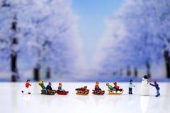 Gente miniatura: Muñeco de nieve y gente de los niños que juega alrededor de s Imagenes de archivo