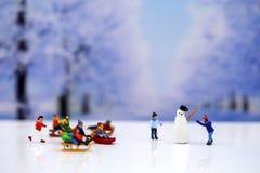 Gente miniatura: Muñeco de nieve y gente de los niños que juega alrededor de s Imagen de archivo libre de regalías