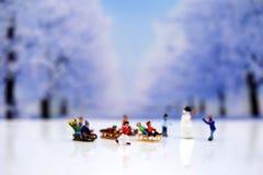 Gente miniatura: Muñeco de nieve y gente de los niños que juega alrededor de s Foto de archivo libre de regalías