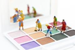 Gente miniatura: Mujeres que limpian las herramientas, sombreador de ojos Uso para la belleza, producto cosmético de la imagen Foto de archivo libre de regalías