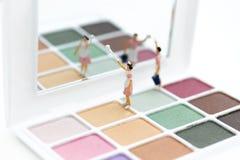 Gente miniatura: Mujeres que limpian las herramientas, sombreador de ojos Uso para la belleza, producto cosmético de la imagen Fotografía de archivo libre de regalías