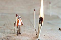 Gente miniatura nell'azione con i fiammiferi Fotografia Stock Libera da Diritti