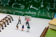Gente miniatura: niños con el bolso de escuela que se coloca en el libro fotografía de archivo