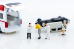 Gente miniatura: Personale danneggiato dagli incidenti stradali, ambulanza trasportata all'ospedale per il trattamento fotografia stock