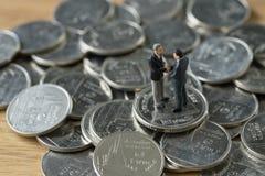 Gente miniatura: piccola figura handshake degli uomini d'affari sulla pila Immagine Stock Libera da Diritti