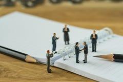 Gente miniatura, piccola figura handshake dell'uomo d'affari ed altra Immagini Stock Libere da Diritti