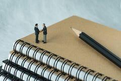 Gente miniatura: Piccola figura handshake e supporto degli uomini d'affari Immagini Stock