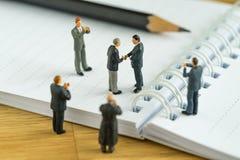 Gente miniatura: Piccola figura handshake ed altro degli uomini d'affari Fotografie Stock Libere da Diritti