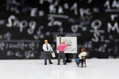 Gente miniatura: Proceso del trabajo del planeamiento del hombre de negocios El uso de la imagen para encontrar la solución/soluc imagenes de archivo