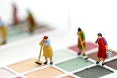 Gente miniatura: Pulizia della casalinga o della domestica sui prodotti di bellezza immagine stock