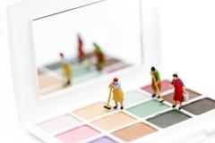 Gente miniatura: Pulizia della casalinga o della domestica sui prodotti di bellezza fotografia stock