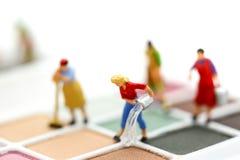 Gente miniatura: Pulizia della casalinga o della domestica sui prodotti di bellezza fotografia stock libera da diritti