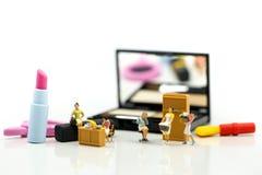 Gente miniatura: Pulizia della casalinga o della domestica sui prodotti di bellezza fotografie stock