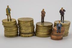 Gente miniatura que se sienta en monedas de la pila fotografía de archivo libre de regalías