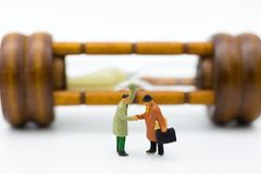 Gente miniatura: Sacudida de la mano del hombre de negocios con el fondo del reloj de arena Uso de la imagen por hora de invertir Imagen de archivo
