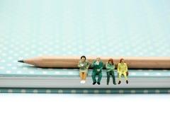 Gente miniatura: sedendosi sul libro e sulla matita facendo uso come di backgrou Fotografia Stock